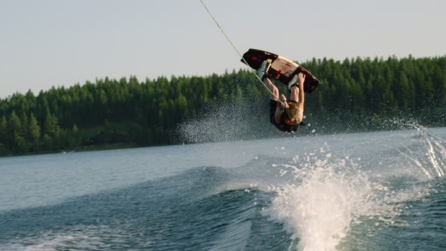 a twenty-something caucasian male jumps and performs tricks on a wakeboard before falling on glen lake near victor, montana on a sunny afternoon - wassersport stock-videos und b-roll-filmmaterial