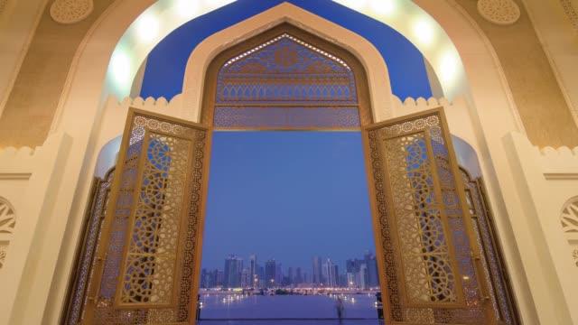 vidéos et rushes de panorama de la porte d'entrée twilight illumination doha ville mosquée 4 temps k caduc qatar - doha