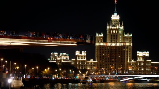 twilight view of the building kotelnicheskaya embankment and the soaring bridge at the moscow river. - rzeka moskwa filmów i materiałów b-roll