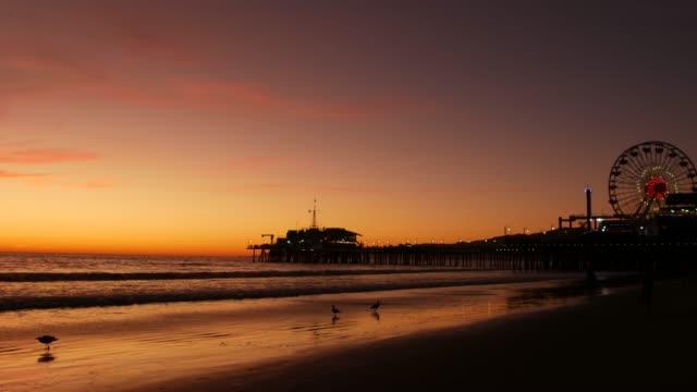 Twilight waves against classic illuminated ferris wheel, amusement park on pier in Santa Monica pacific ocean beach resort. Summertime iconic symbol of California glowing in dusk, Los Angeles, CA USA.