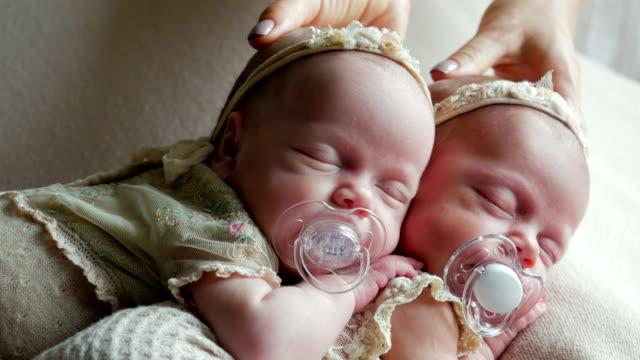 les bébés jumeaux dorment dans le berceau en robes - Vidéo