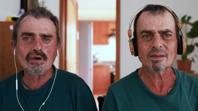 Twin brother senior men talking on a video call while wearing headphones