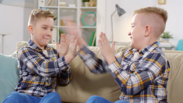 twin brothers playing clapping game at home - gemelle video stock e b–roll