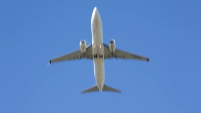 das flugzeug des zweimotorigen düsenflugzeugs, das in blauem himmel über den kopf fliegt - vorbeigehen stock-videos und b-roll-filmmaterial
