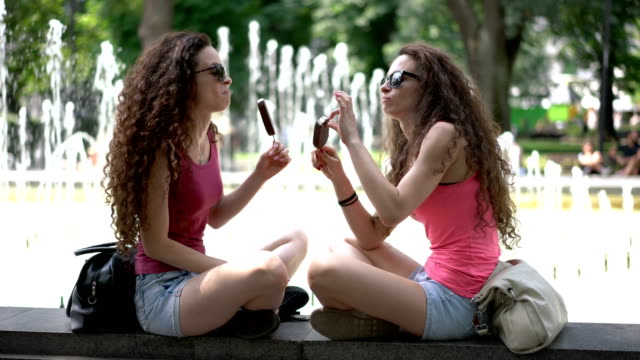 Twin sisters eating ice-creams while sitting at the park fountains Beautiful young women relaxing in the park and eating ice-creams sister stock videos & royalty-free footage