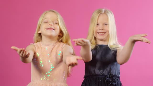 tvillingar i party outfits blåser kyssar - blåsa en kyss bildbanksvideor och videomaterial från bakom kulisserna