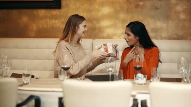 två unga kvinnor som går igenom menyn på en fin restaurang, medan dricka ett glas rödvin och skrattar och pratar, kanske skvallra och utbyta presenterar på ett speciellt tillfälle - spendera pengar bildbanksvideor och videomaterial från bakom kulisserna