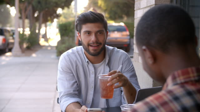 Two adult male friends talking over cold drinks outside cafe video