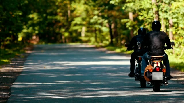 Two adult men motorcyclists riding motorbikes in the forest at the bright sunny day