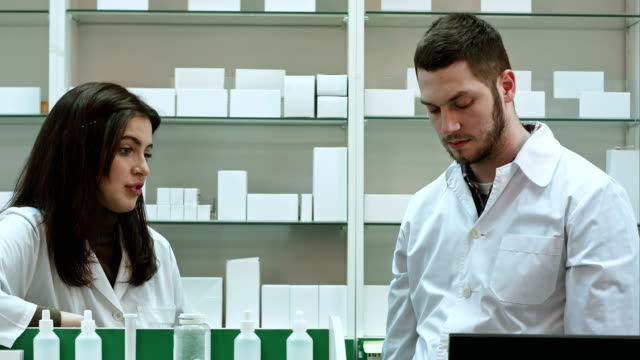 Two adult pharmacists having conflict, discussing problems at pharmacy video