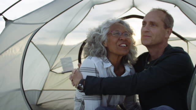 two adventurous seniors snuggling in their tent - baby boomer stock videos and b-roll footage