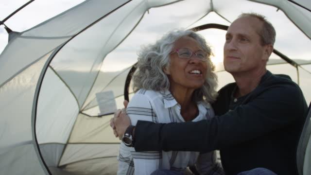 två äventyrliga seniorer snuggling i deras tält - aktiva pensionärer utflykt bildbanksvideor och videomaterial från bakom kulisserna