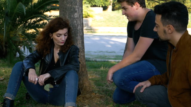 two affectionate friends comforting their sad friend in the park - sostegno emotivo video stock e b–roll