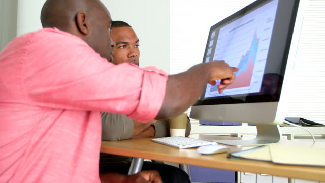 Two African American Business men looking at data on computer video