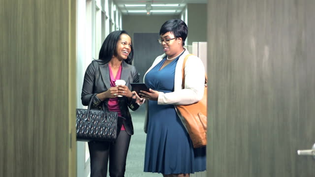 Two African American business women meeting Two African-American mid adult businesswomen having a meeting in an office board room. A heavyset woman wearing eyeglasses is standing, conversing with a woman sitting at the conference table. They look at a digital tablet and smile. office cubicle stock videos & royalty-free footage