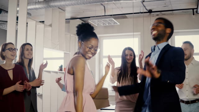 Two African American colleagues dancing together at casual office party. Diverse friends share fun time at work 4K Two African American colleagues dancing together at casual office party. Diverse friends share fun time at work 4K. Young happy millennial multiethnic business people doing funny dance at a coworking. promotion employment stock videos & royalty-free footage