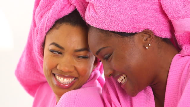 Two African American friends in spa smiling with heads together video