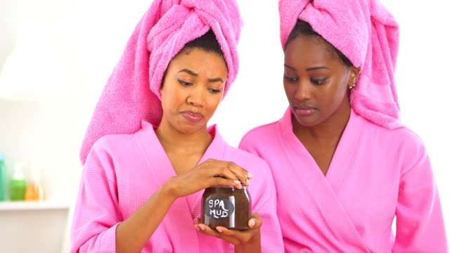 Two African American friends open spa mud and smell it video