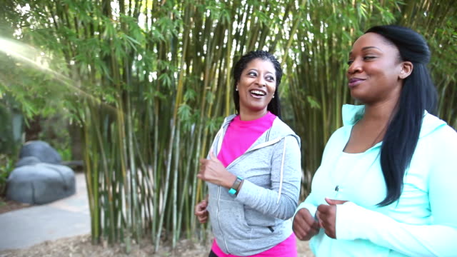 Two African American women power walking in park video
