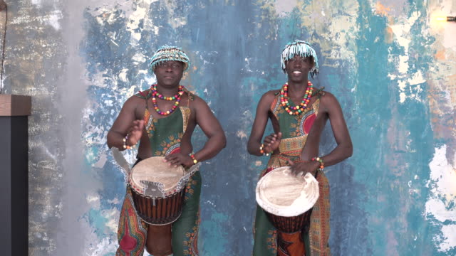 Two African artists in colorful costumes playing djemba drums Two African artists in colorful costumes playing djemba drums, medium shot minority groups stock videos & royalty-free footage