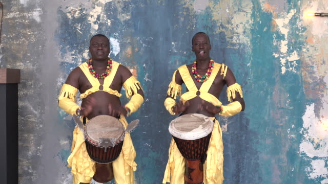 Video Two African artists in colorful costumes playing djemba drums