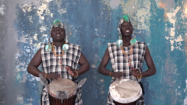 Two African artists in colorful costumes playing djemba drums