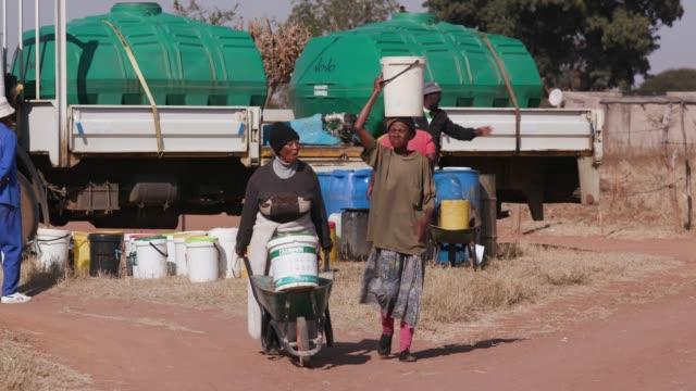 플라스틱 양동이에 유조선에서 물을 수집 하 고 그들의 가정 등을 맞댄 걷는 2 아프리카 여자 - 환경 피해 스톡 비디오 및 b-롤 화면