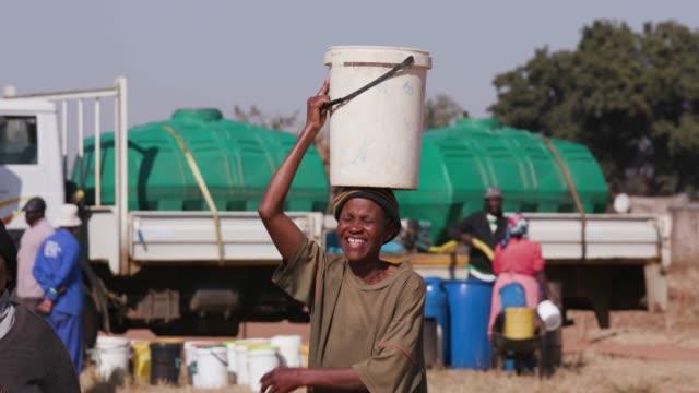 Dos Mujer Africana Recogiendo Agua De Una Cisterna En Baldes Plásticos Y  Caminando Hacia Sus Casas Vídeo Stock y más Footage de Accidentes y  desastres - iStock