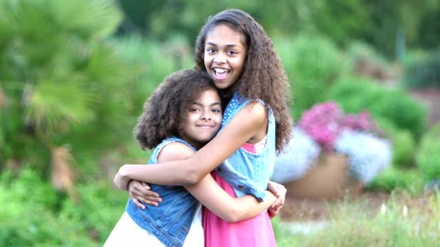 two african-american sisters smiling in garden - serdeczny filmów i materiałów b-roll