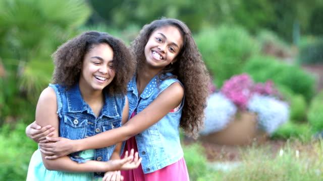 2 人の姉妹のアフリカ系アメリカ人が庭に笑みを浮かべて - 兄弟姉妹点の映像素材/bロール
