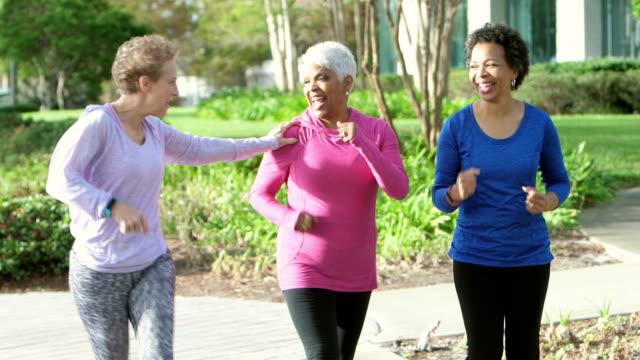 vídeos de stock e filmes b-roll de two african-american women power walking, friend runs by - 55 59 anos