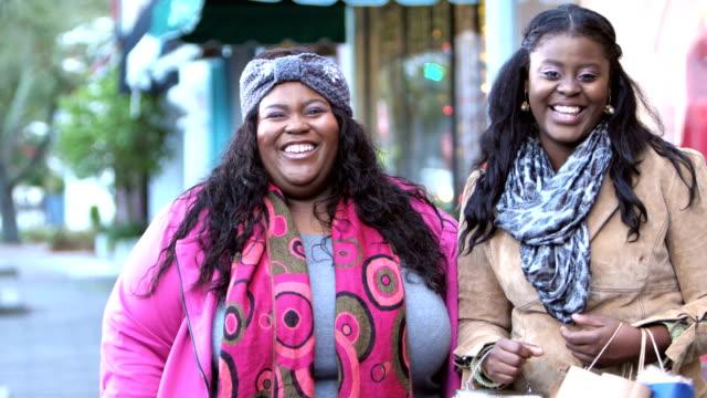 zwei afroamerikanerinnen einkaufen in der stadt - übergrößen model stock-videos und b-roll-filmmaterial