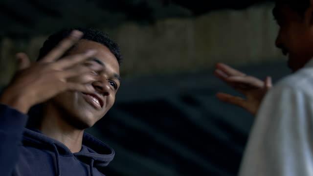 due amici maschi afro-americani sorridenti e pugni urtanti, gesto di saluto - pugno video stock e b–roll