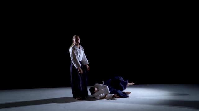 Two Aikido Masters participants of the training in special clothes of aikido hakama work out the methods of single combat