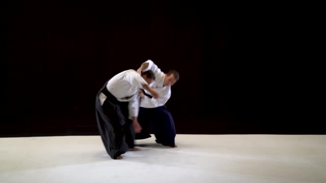 Two Aikido Masters technique demonstration on black and white studio