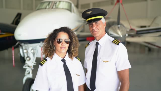 Two airplane pilots in a hangar and looking at camera