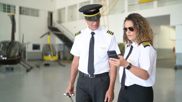 Two airplane pilots talking and walking in a hangar