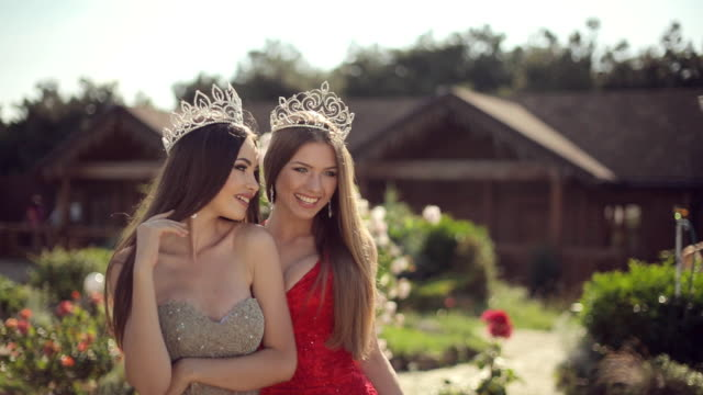 two amazing girls in a long gowns and crowns laughing in the park with roses - prom fashion stock videos and b-roll footage