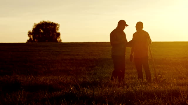 Two American farmers communicate in the field at sunset. Next to them is a shovel video