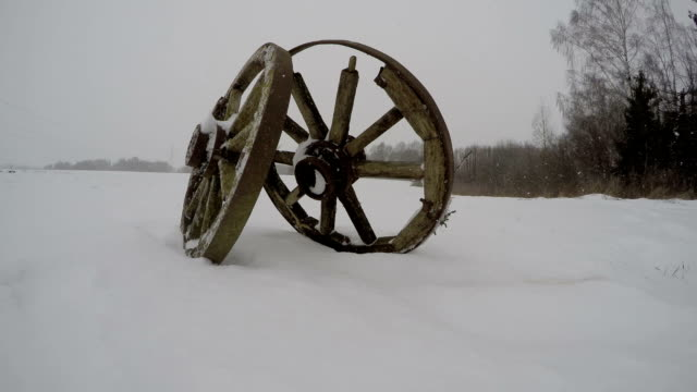 Two antique wooden wheels in the snow, time lapse video