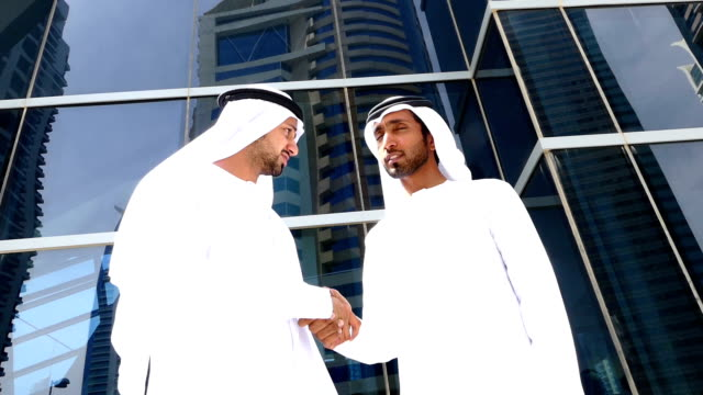Two arab business people in handshake on the street -slowmotion video