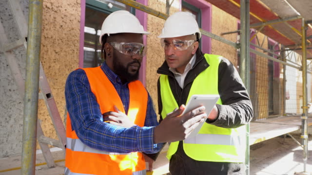 Two architects, a black and a white, on construction site among scaffolding video