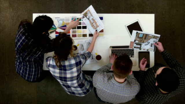 Dois arquitetos layout discutindo enquanto colegas de trabalho femininas, olhando para a paleta de cores - vídeo