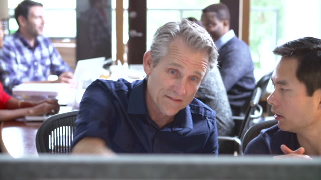 Two Architects Working At Desk With Meeting In Background video