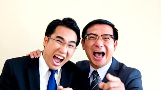 Two Asian business men are standing laughing madly. And a finger pointing to camera