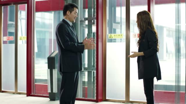 2 つのアジア ビジネス人立っていると話して ビデオ