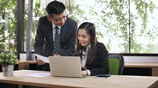 Two Asian business people talking video