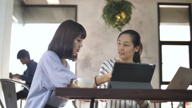 2 アジアのビジネス人、一緒にカフェで働いてスローモーションします。 ビデオ