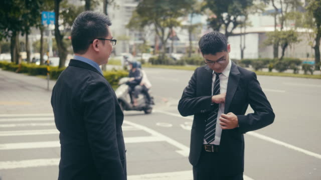 Two asian businessmen exchanging business cards in the street Video series of a business-on-the-go concept where  asian businessmen are exchanging business cards, suing smart phone, taking selfies, and rushing across the street. Shot in the Taipei financial district. business card stock videos & royalty-free footage