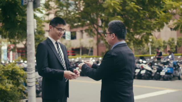 two asian businessmen exchanging business cards in the street - business card stock videos & royalty-free footage